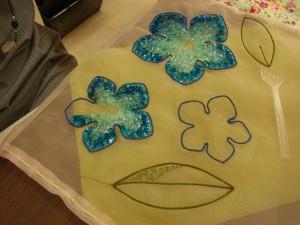 もう一方の課題は、'青いhana'のチャームを刺しています。3枚の花びらと葉を組み合わせた物と、もう片方の小さい花を繋ぎチャームを作ります。